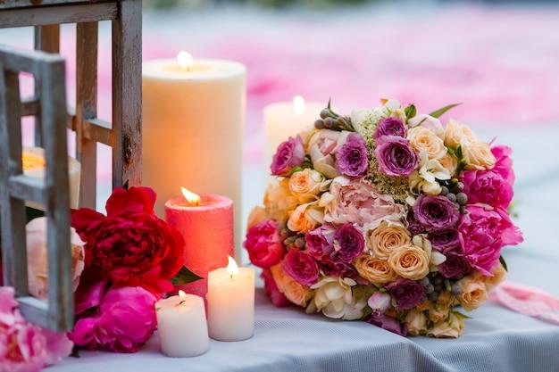 Bukiet ślubny wśród dekoracji ze świecami i świeżymi kwiatami