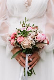 Bukiet ślubny z białych i różowych róż i piwonii w rękach panny młodej na tle białej sukni
