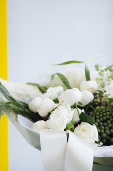 Bukiet ślubny z białych róż i eukaliptusa na szarym tle widok z boku. poranne przygotowania panny młodej. szczegóły stylowego europejskiego dnia ślubu.