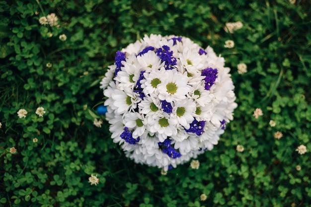 Bukiet ślubny z białych stokrotek i niebieskich kwiatów