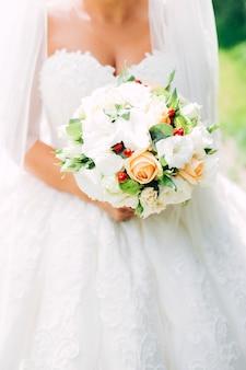 Bukiet ślubny z białymi goździkami i ranunculi. delikatny bukiet w kolorze żółtym i białym. liście eukaliptusa.