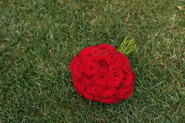 Bukiet ślubny z czerwonych róż na zielonej trawie