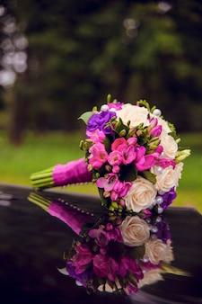 Bukiet ślubny z czerwonymi różami leżącymi na samochodzie