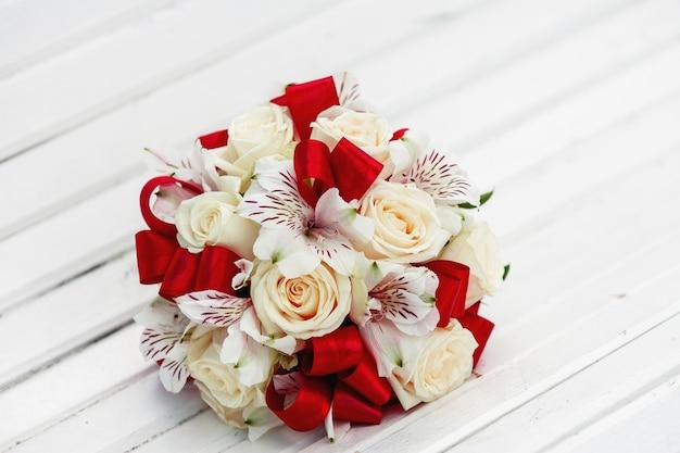 Bukiet ślubny z czerwonymi wstążkami, beżowymi różami i storczykami
