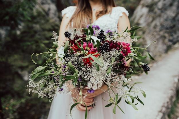 Bukiet ślubny z jesiennych kwiatów w rękach panny młodej