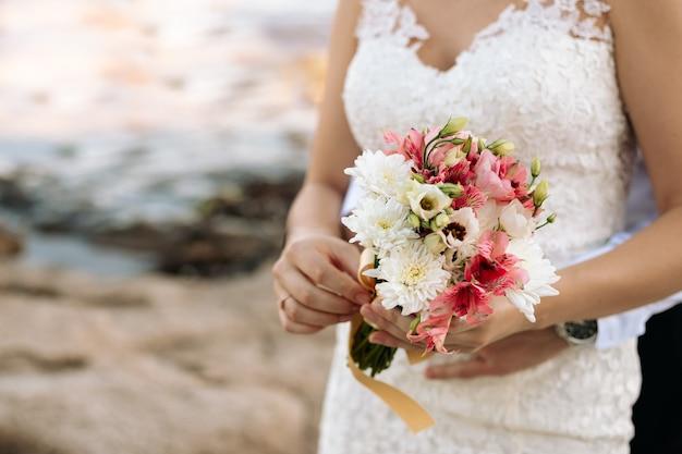 Bukiet ślubny z kwiatów w rękach panny młodej