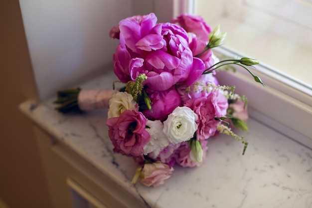 Bukiet ślubny z piwoniami i różami leżącymi w oknie na parapecie