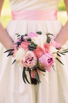 Bukiet ślubny z piwonii w rękach panny młodej