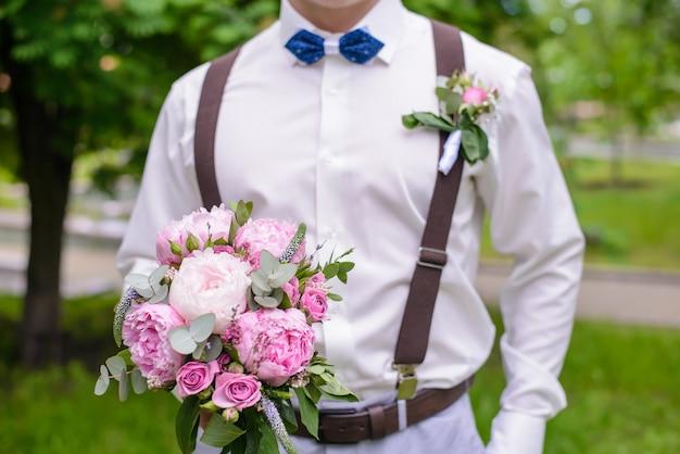 Bukiet ślubny z piwonii w ręku pana młodego