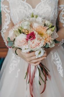 Bukiet ślubny z różnych kwiatów z bliska w rękach panny młodej.