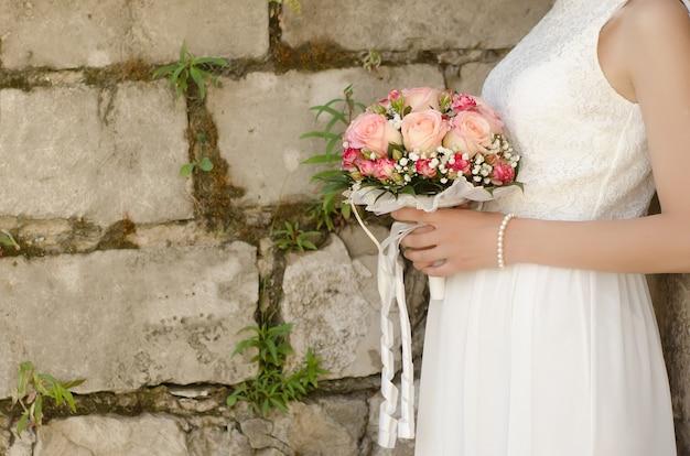 Bukiet ślubny z różowych róż w rękach panny młodej z bliska na tle kamiennego muru