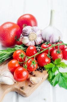 Bukiet soczystych organicznych czerwonych pomidorków cherry z zielonym rozmarynem, czosnkiem i przyprawami na białym starym stole. składniki do gotowania. koncepcja czystego jedzenia. dieta wegetariańska. miejsce na tekst