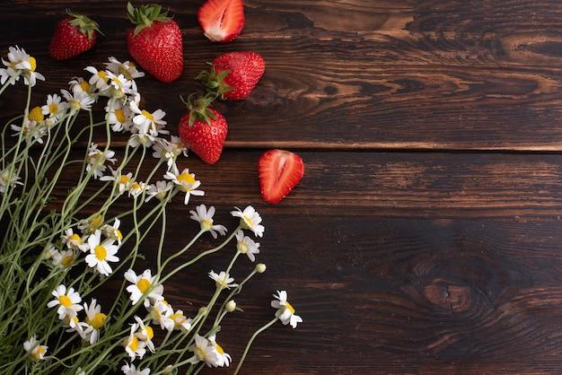 Bukiet stokrotek z truskawkami na ciemnym tle drewnianych, koncepcja lato, miejsce, z bliska.