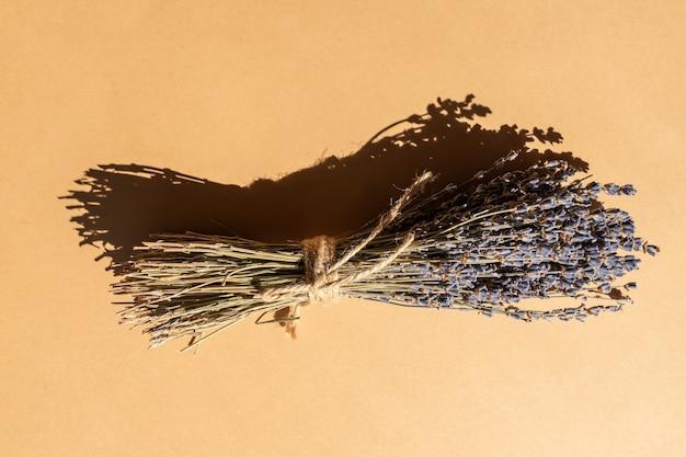 Bukiet suchej lawendy wbity naturalną liną na beżowym tle. aromaterapia i medycyna alternatywna.