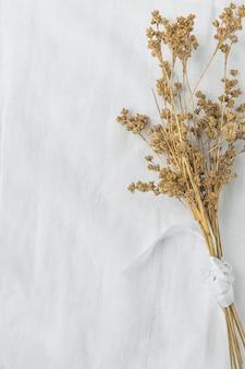 Bukiet suchych beżowych brązowych kwiatów wiązanych jedwabną wstążką na tle białej tkaniny lnianej.