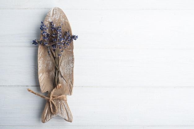 Bukiet suchych fioletowych kwiatów lawendy ułożonych na rustykalnym talerzu na białym stole