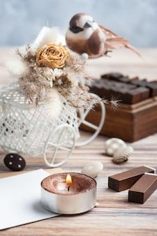 Bukiet suchych kwiatów na ozdobnym rowerze z małym brązowym ptaszkiem i zapaloną świeczką na stole. kartka okolicznościowa na ślub lub wakacje w naturalnych kolorach