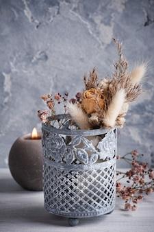 Bukiet suchych kwiatów w blaszanym wazonie na białym drewnianym stole