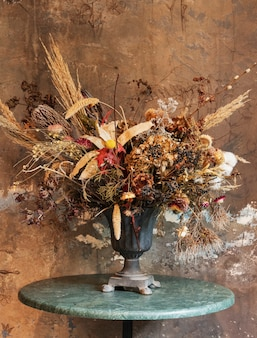 Bukiet suchych kwiatów w wazonie przy grunge brązowej ścianie
