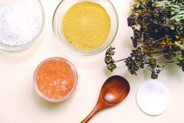 Bukiet suszonych kwiatów, drewniana łyżka i szklane miski z naturalnymi produktami do mieszania i tworzenia naturalnych masek i kremów