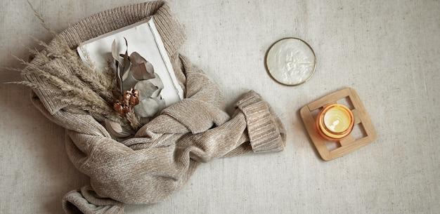 Bukiet suszonych kwiatów na ciepłym pastelowym swetrze i widoku z góry świecy, koncepcja przytulności jesieni