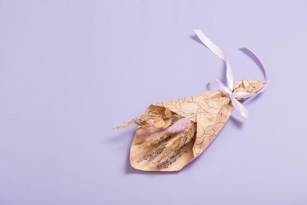 Bukiet suszonych kwiatów w papierze rzemieślniczym na liliowym tle