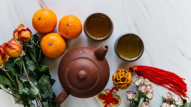 Bukiet suszonych róż; cała pomarańcza; kutas; gliniany czajniczek i filiżanki herbaty na marmurowym tle