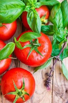 Bukiet świeżych dojrzałych kolorowych organicznych pomidorów z kropli wody