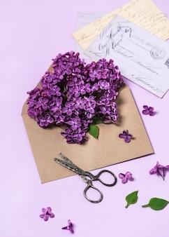 Bukiet świeżych fioletowych kwiatów bzu w rzemieślniczej kopercie i rustykalnych nożyczkach