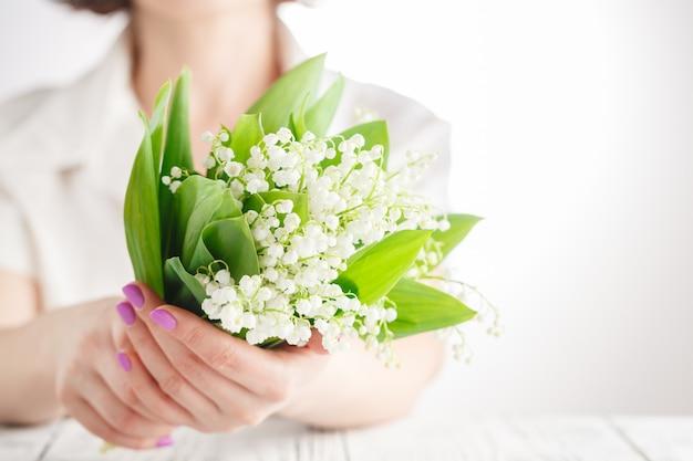 Bukiet świeżych konwalii w rękach młodej kobiety w białej sukni. ścieśniać. symbol nadejścia wiosny i ciepła.