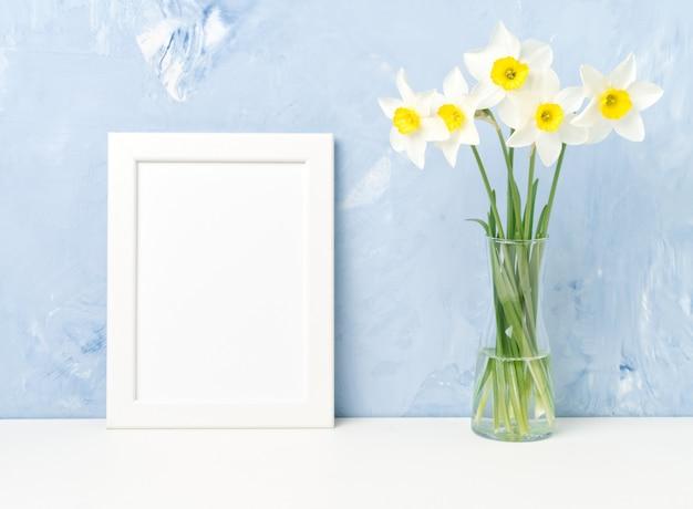 Bukiet świeżych kwiatów, biała ramka na stole, naprzeciwko niebieska teksturowana betonowa ściana. pusty