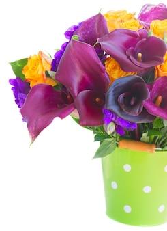 Bukiet świeżych kwiatów calla lilly, róż i eustoma w zielonej doniczce z bliska na białym tle