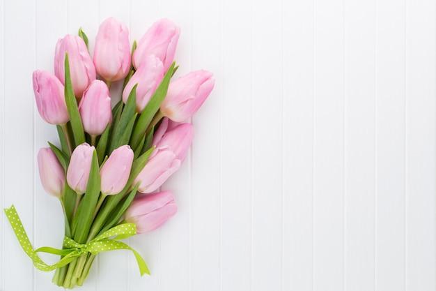 Bukiet świeżych kwiatów tulipanów różowy na półce przed drewnianą ścianą.
