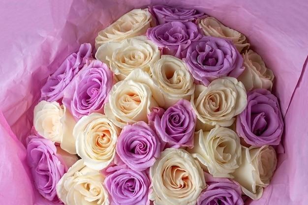 Bukiet świeżych niesamowitych białych i fioletowych róż w papierze rzemieślniczym na ciemnym tle na pocztówkę, okładkę, baner. piękne kwiaty jako prezent