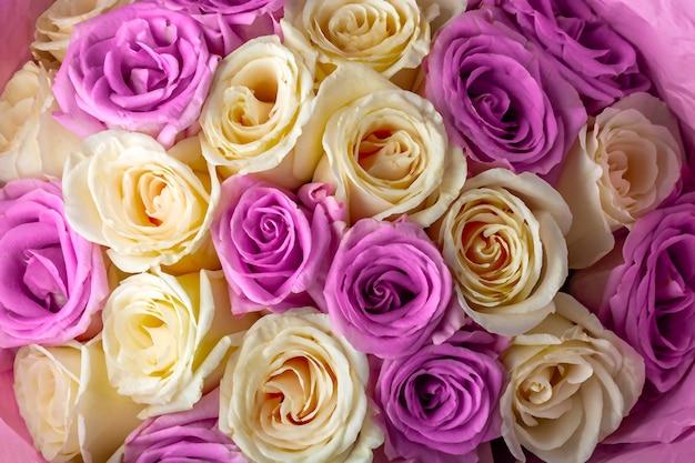 Bukiet świeżych niesamowitych białych i fioletowych róż w ręcznie robionym papierze
