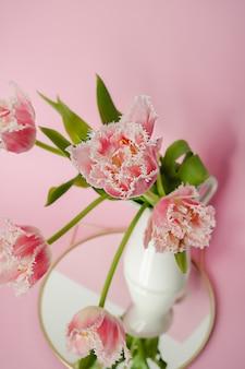 Bukiet świeżych papug tulipanów z zielonymi liśćmi w białym ceramicznym dzbanku stojącym na okrągłym lustrze na tle różowego papieru. kwiatowa geometryczna kompozycja dekoracyjna.