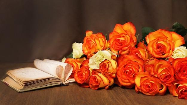 Bukiet świeżych pomarańczowych róż na stole z otwartą książką