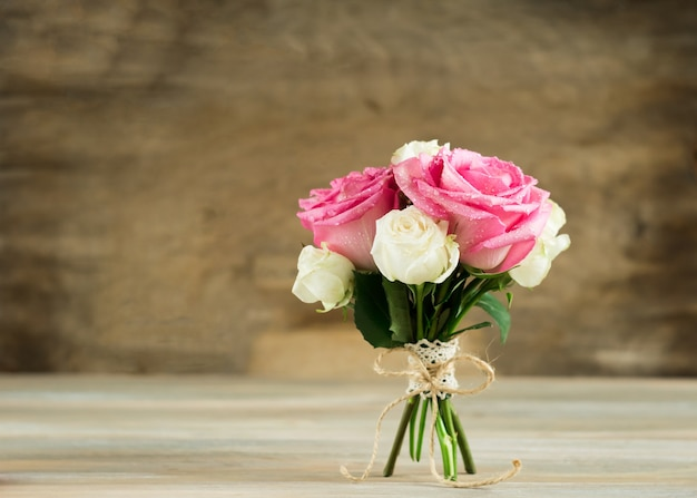 Bukiet świeżych róż jest bandażowany wstążką na drewnianym tle