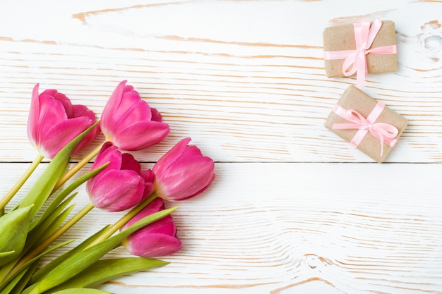 Bukiet świeżych różowych tulipanów i kilka zapakowanych prezentów na białym drewnie, widok z góry
