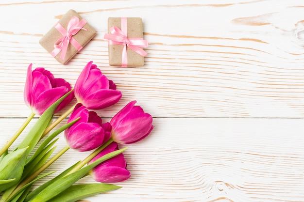 Bukiet świeżych tulipanów i kilka zapakowanych prezentów z różową wstążką na białym drewnie, widok z góry
