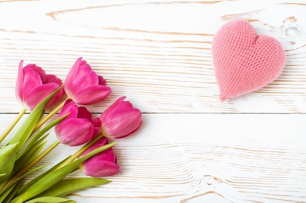 Bukiet świeżych tulipanów i różowe serce z dzianiny na białym drewnie, widok z góry