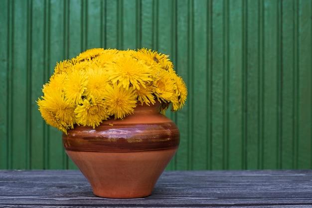 Bukiet świeżych żółtych mleczy w glinianym garnku na zielonym drewnianym tle, latem
