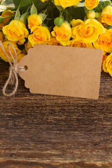 Bukiet świeżych żółtych róż obramowania na drewnie z pustą notatką papieru