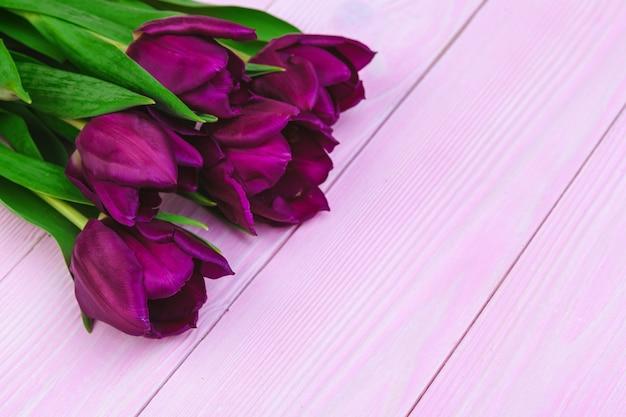 Bukiet tulipan kwitnie na różowym drewnianym tle z copyspace