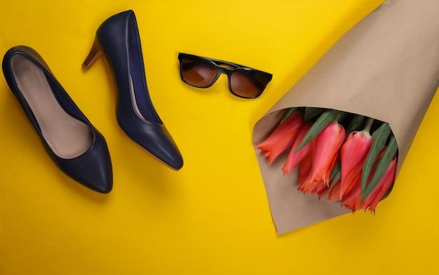 Bukiet tulipanów, buty na wysokim obcasie z okularami przeciwsłonecznymi na żółto