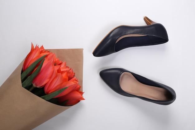 Bukiet tulipanów i buty na wysokim obcasie na białym tle. święto matki lub 8 marca, urodziny. widok z góry