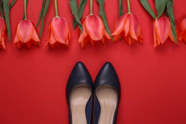 Bukiet tulipanów i buty na wysokim obcasie na czerwonym tle. święto matki lub 8 marca, urodziny. widok z góry