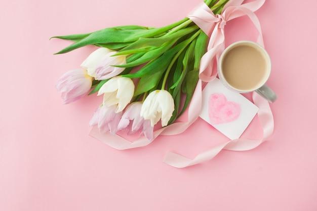 Bukiet tulipanów i filiżanka kawy na różowym tle pastelowych.
