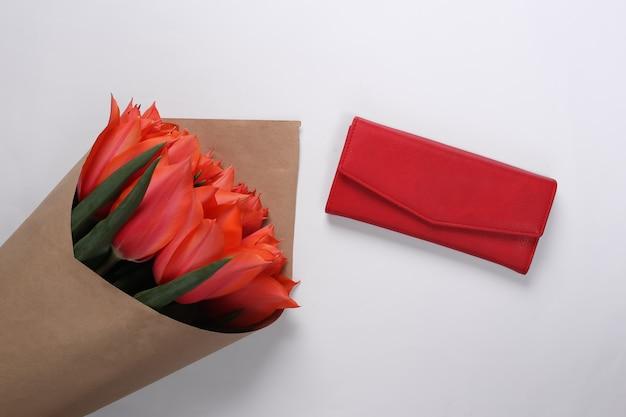 Bukiet tulipanów i torebka na białym tle. święto matki lub 8 marca, urodziny. widok z góry