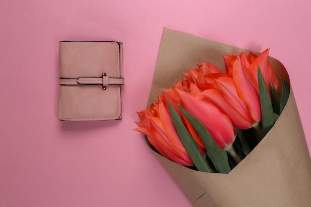 Bukiet tulipanów i torebka na różowym pastelowym tle. święto matki lub 8 marca, urodziny. widok z góry